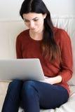 Kvinna som hemma arbetar på en bärbar dator Arkivfoto