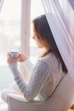 Kvinna som hemma dricker kaffe i ottan Royaltyfri Foto