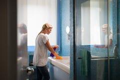 Kvinna som hemma gör sysslor och gör ren badrummen Royaltyfri Bild