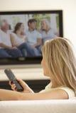 Kvinna som hemma håller ögonen på Widescreen TV Arkivbilder