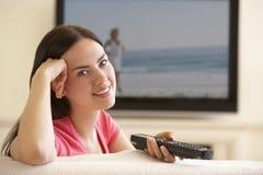 Kvinna som hemma håller ögonen på Widescreen TV Arkivfoton