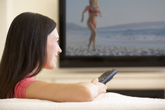 Kvinna som hemma håller ögonen på Widescreen TV Arkivbild