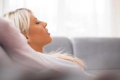 Kvinna som hemma kopplar av på soffan Royaltyfri Fotografi