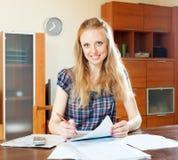 Kvinna som hemma läser det finansiella dokumentet Royaltyfri Bild