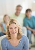 Kvinna som hemma ler med familjsammanträde i bakgrund royaltyfri bild