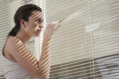 Kvinna som hemma plirar till och med rullgardiner Royaltyfri Foto