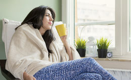 Kvinna som hemma sitter, slåget in i en filt som dricker te Royaltyfria Bilder