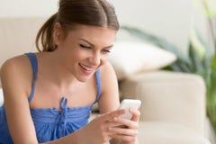 Kvinna som hemma spelar mobillekar på mobiltelefonen arkivfoton