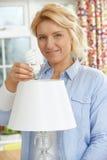 Kvinna som hemma sätter lightbulben för låg energi in i lampan Fotografering för Bildbyråer