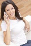 Kvinna som hemma talar på den mobila celltelefonen Fotografering för Bildbyråer