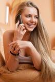 Kvinna som hemma talar på mobiltelefonen Arkivbild