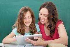 Kvinna som hjälper flickan, i att använda den digitala minnestavlan Fotografering för Bildbyråer