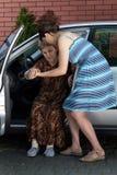 Kvinna som hjälper handikappade personer för att få ut ur bilen Arkivbild