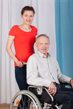 Kvinna som hjälper handikappade personer i en rullstol Fotografering för Bildbyråer