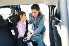 Kvinna som hjälper hennes dotter att fästa bilbälten arkivbild