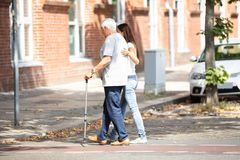 Kvinna som hj?lper hennes fader While Crossing Road arkivfoton
