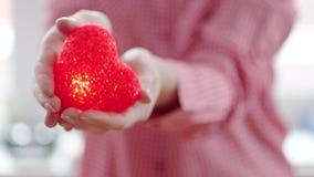 Kvinna som håller en hjärta för ` s i henne händer stock video