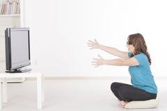 Kvinna som håller ögonen på TV:N 3D i exponeringsglas Arkivfoton