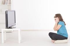 Kvinna som håller ögonen på TV:N 3D i exponeringsglas Royaltyfri Bild