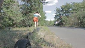Kvinna som hoppar över gummihjul lager videofilmer