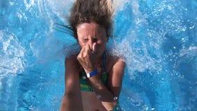 Kvinna som hoppar in i en pöl för blått vatten lager videofilmer