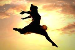Kvinna som hoppar på solnedgången Royaltyfri Bild