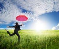 Kvinna som hoppar till den blåa skyen med det röda paraplyet Royaltyfria Bilder