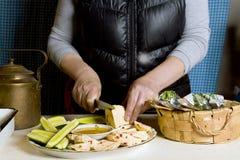 Kvinna som hugger av ost royaltyfri foto