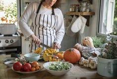 Kvinna som hugger av pumpor i köket arkivbild