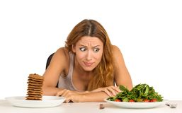 Kvinna som huruvida avgör att äta sund mat eller söta kakor Arkivfoto