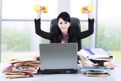 Kvinna som i regeringsställning arbetar och övar Arkivbild