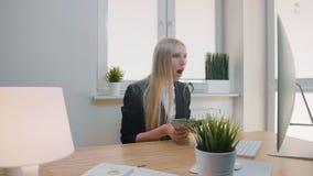 Kvinna som i regeringsställning firar framgång Elegant blont kvinnligt sammanträde på arbetsplatsinnehavet i handpacke av kontant lager videofilmer
