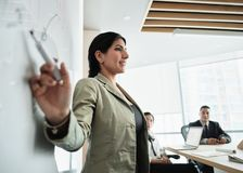 Kvinna som i regeringsställning gör presentation med mötesrum för bräde arkivbild