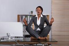 Kvinna som i regeringsställning mediterar royaltyfri foto