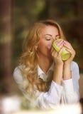 Kvinna som inomhus dricker kaffe och att tycka om aromen av drycken Royaltyfri Bild