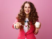 Kvinna som isoleras på den rosa geende skeden med organisk yoghurt för lantgård Royaltyfri Bild
