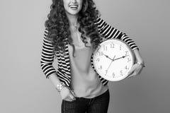 Kvinna som isoleras på med klockan som ser kopieringsutrymme arkivfoton