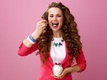 Kvinna som isoleras på rosa bakgrund som äter organisk yoghurt för lantgård Arkivfoton