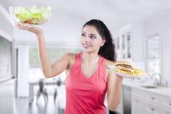 Kvinna som jämför den nya sallad och hamburgaren Fotografering för Bildbyråer