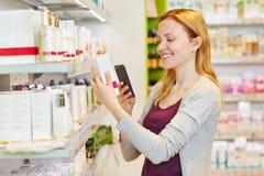 Kvinna som jämför priser med smartphonen i apotek royaltyfri bild