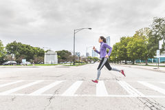 Kvinna som joggar och korsar vägen på sebra i Chicago Royaltyfri Foto