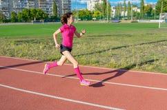 Kvinna som joggar på spåret som kör på stadion arkivfoton