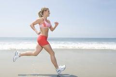 Kvinna som joggar på stranden Royaltyfria Bilder