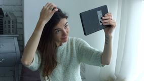 Kvinna som justerar hennes hår genom att använda minnestavlan som spegeln stock video