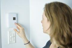 Kvinna som justerar termostaten på system för hem- uppvärmning arkivfoto