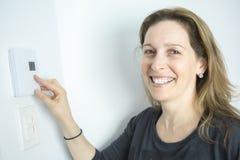 Kvinna som justerar termostaten på system för hem- uppvärmning royaltyfri foto