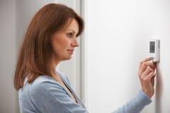Kvinna som justerar termostaten på centralvärme Arkivbilder