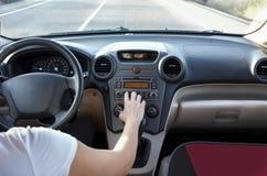 Kvinna som justerar volym på billjudsignalsystemet, medan hon kör royaltyfri foto