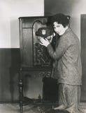 Kvinna som justerar volym på 20-talradio Fotografering för Bildbyråer