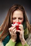 Kvinna som känner sig sjuk med en förkylning som slås in upp i en ullig halsduk och Arkivfoton